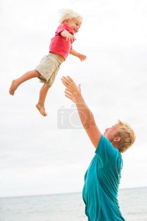 Photo pour Père et fils jouant sur la plage - image libre de droit