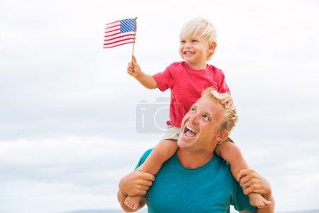 Photo pour Père et fils jouent sur la plage avec le drapeau américain. Les USA célèbrent le 4 juillet . - image libre de droit