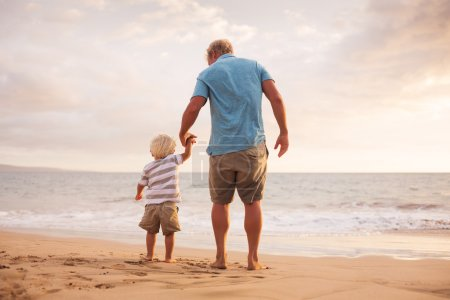 Photo for Happy father and son walking on the beach at sunset - Royalty Free Image