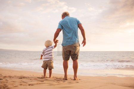 Foto de Feliz padre e hijo caminando por la playa al atardecer - Imagen libre de derechos