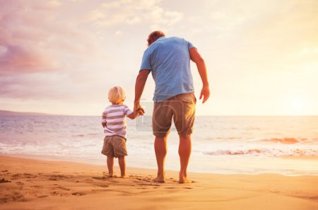 Photo for Father and son standing on the sea shore holding hands at sunset - Royalty Free Image