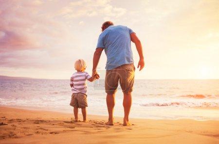 Photo pour Père et fils debout sur le bord de la mer tenant la main au coucher du soleil - image libre de droit