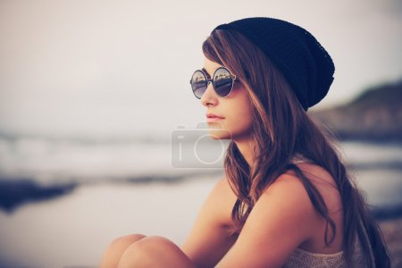 Photo for Fashion portrait of young hipster woman with hat and sunglasses on the beach at sunset, retro style color tones - Royalty Free Image