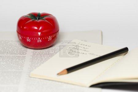 Photo pour Pomodoro (tomate) technique est une méthode d'étude qui aide à éviter la temporisation à l'aide d'une minuterie de cuisine - image libre de droit