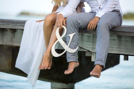 Photo pour Jeune couple assis sur le pont avec signe d'ampersand - image libre de droit