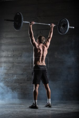 Photo for Athlete performs a barbell exercise. Shot from behind. - Royalty Free Image