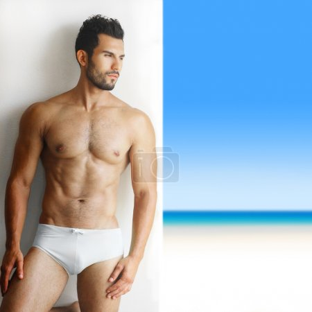 Photo pour Portrait sexy d'un modèle masculin torse nu très musclé en sous-vêtements contre mur blanc en pose sensuelle avec paradis tropical en arrière-plan - image libre de droit