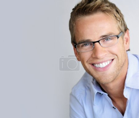 Photo for Young handsome man with great smile wearing fashion eyeglasses against neutral background with lots of copy space - Royalty Free Image