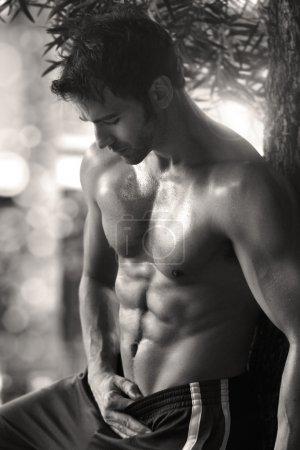 Photo pour Sexy sensuel portrait extérieur d'un modèle masculin très ajustement torse nu montrant abdos - image libre de droit