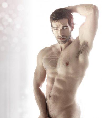 Photo pour Musclé jeune homme mignon nu sexy contre fond abstrait moderne lumineux - image libre de droit
