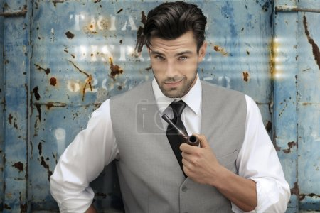 Photo for Portrait of a confident classically handsome male model holding a pipe in upscale clothing - Royalty Free Image