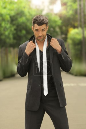 Photo for Fashion portrait of a sexy male model in black suit with loose white tie - Royalty Free Image