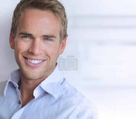 Photo pour Portrait d'un grand homme à la recherche de jeune confiant avec grand sourire réel - image libre de droit