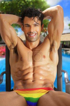 Photo pour Souriant heureux bel homme musclé dans les maillots de bain arc-en-ciel dans un cadre de villégiature dynamique - image libre de droit