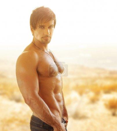 Photo pour Homme musclé sexy avec un grand corps en plein air dans la lumière dorée - image libre de droit