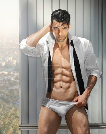 Photo pour Magnifique modèle masculin musclé en culotte révélatrice en pose provocante avec chemise ouverte - image libre de droit
