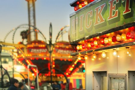 Photo for Scene at a classic carnival with rides and focus on ticket booth with subtle retro styling - Royalty Free Image