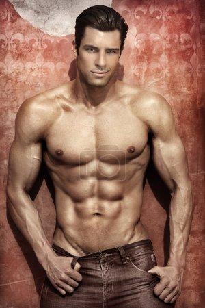 Foto de Handsome muscular man posing against vibrant elegant background - Imagen libre de derechos
