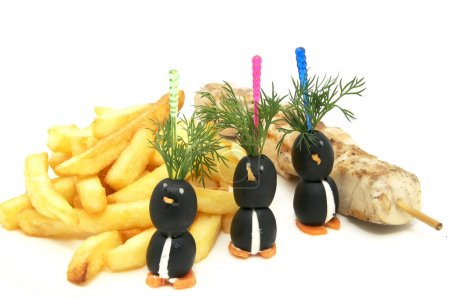 French fries and kebabs of chicken and olives