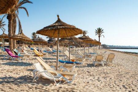 Photo pour Plage de sable fin avec transats et parasols au coucher du soleil - image libre de droit