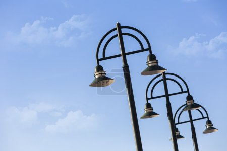 Modern light poles against a blue sky...
