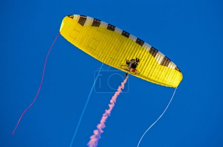 Motorized hang-glider in blue sky.