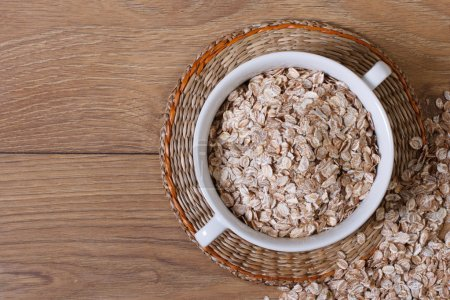 Oat flakes in a bowl and scattered on the table. top view