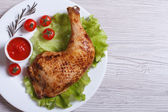 chicken leg with rosemary, lettuce and tomato. top view