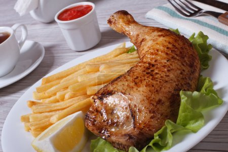Portion of French fries with chicken leg and lemon