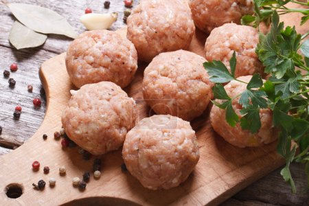 Raw meatballs on a chopping board and ingredients....