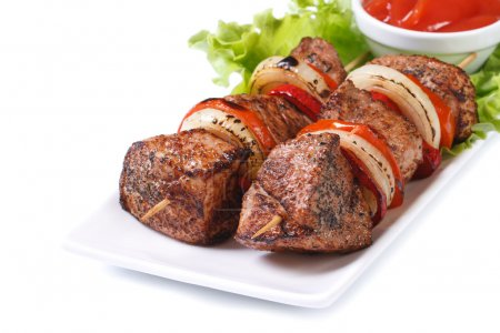 skewers of meat with vegetables isolated on white plate