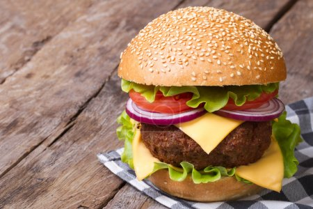 big hamburger with fresh vegetables, cheese and meat