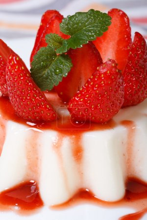 Dessert panna cotta with strawberries and berry syrup. macro