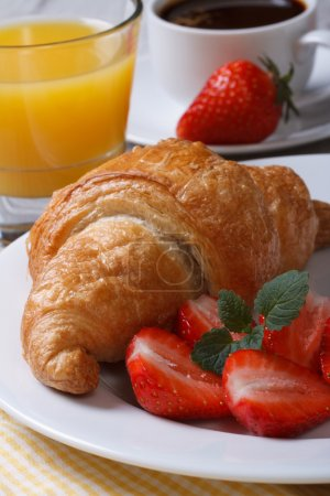 Photo for Continental breakfast: croissants with fresh strawberries, coffee and juice close up vertica - Royalty Free Image