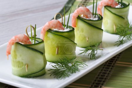 Photo for Appetizer of cucumber rolls with shrimp and cream cheese closeup on a white plate. horizontal - Royalty Free Image
