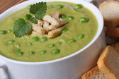 Cream soup with green peas with croutons closeup