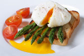 Toast with asparagus, poached egg and tomato closeup