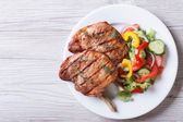 Pork meat grilled with fresh vegetable salad top view