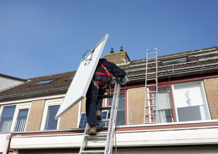 Man climbing the ladder with solar panel