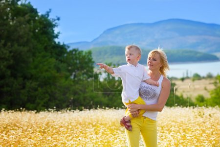 Photo for Mother with son on the camomile meadow - Royalty Free Image