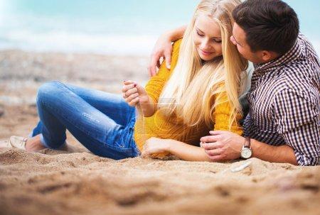Photo pour Couple relaxant sur la plage d'automne - image libre de droit