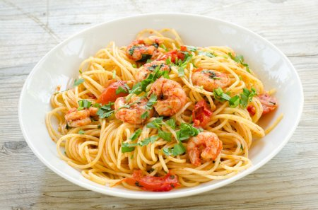 Photo for Pasta dish with shrimps, tomato and parsley - Royalty Free Image