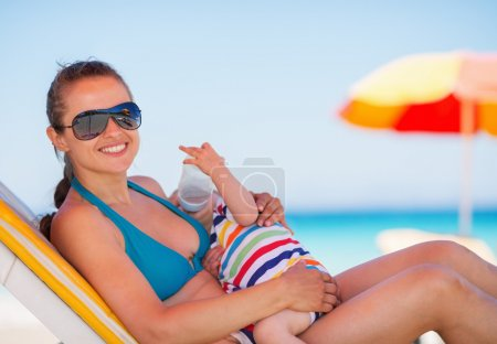 Mother laying on sun bed and holding baby drinking water