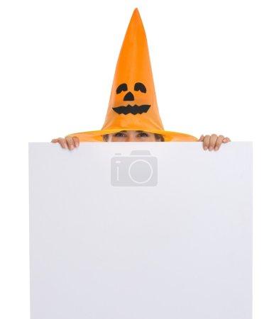Woman in Halloween hat looking out from blank billboard