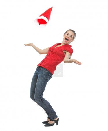 Photo for Happy young woman throwing Santa hat - Royalty Free Image