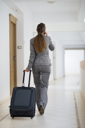 Photo for Business woman in business trip with wheel bag. Rear view - Royalty Free Image