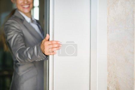 Photo pour Gros plan sur la main de femme d'affaires détenant la porte de l'ascenseur - image libre de droit