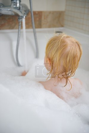 Baby in bath foam. Rear view