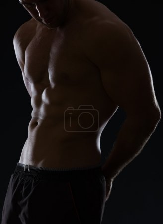 Closeup on male athlete showing muscular body on black