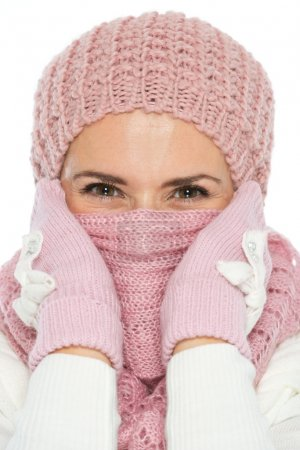 Woman in knit winter clothing closing face with scarf